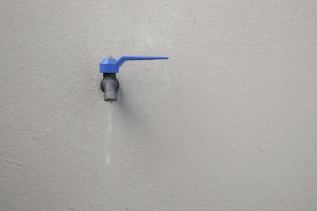 Blue faucet on concrete wall