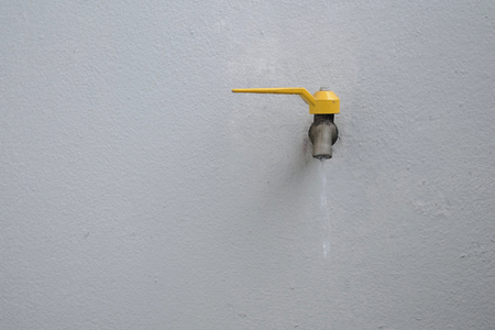 Yellow faucet on concrete wall