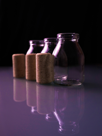 Empty little bottles with cork stopper in purple light