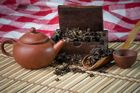 dried tea leaf in small wood box with wooden teaspoon tea pot and cup on bamboo mat