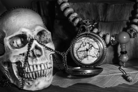 Still life photography pocket watch , bead necklace and blured human skulls in black adn white