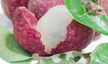 Close up of fresh lychee and peeled showing the red skin and white flesh with green leaf