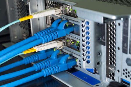 Lan and fiber optic cables are plugged into the back panal of the server.
