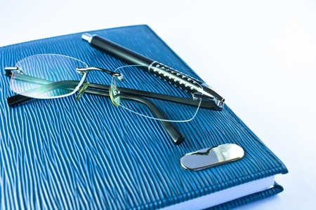 Glasses on blue notebook  with black pen in isolation