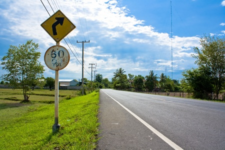 Empty road with a traffic sign  in countryside of Thailand photo