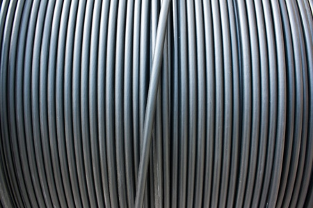 Close-up of black electricity cable vertical on a spool.  Stock Photo