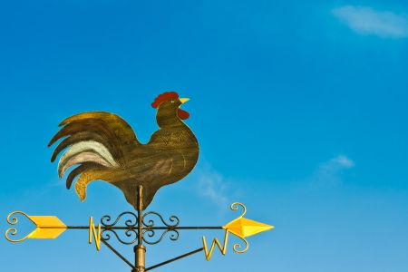a cockerel wind vane against blue sky