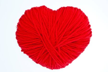Red heart shape symbol made from wool isolated on white background photo