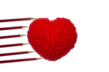Red heart shape symbol made from wool with pencils isolated on white background photo