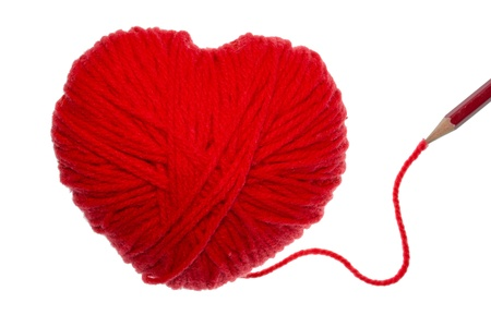Red heart shape symbol made from wool with pencil isolated on white background photo