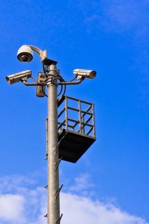 Surveillance Security Camera or CCTV on blue sky photo