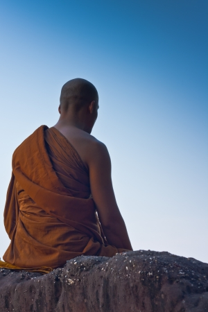 Monk meditating at the top of the mountain