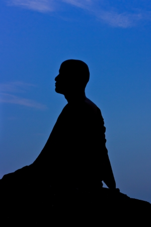 Silhouette of monk meditating at the top of the mountain Stock Photo - 15359822