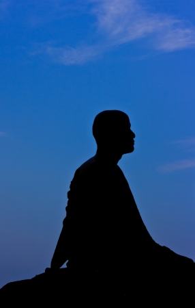 Silhouette of monk meditating at the top of the mountain Stock Photo - 15359846
