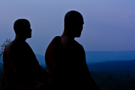 Silhouette of monk meditating at the top of the mountain photo
