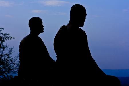 Silhouette of monk meditating at the top of the mountain Stock Photo - 15359853