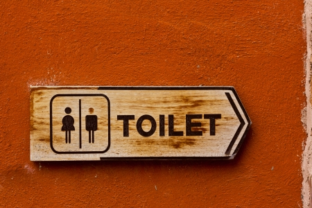Ancient toilet sign on red concrete wall photo