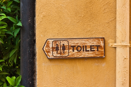 Ancient toilet sign on orange concrete wall photo