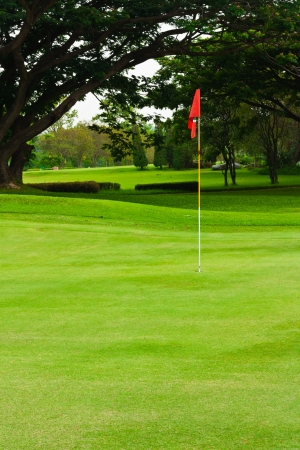 A red flag identifies the hole of a  golf green photo