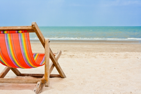 An empty wooden beach chair at the beach Stock Photo