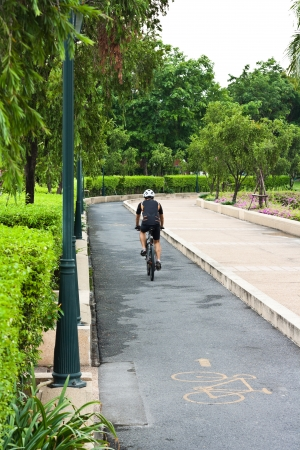 man riding on  bicycle by park, motion blur