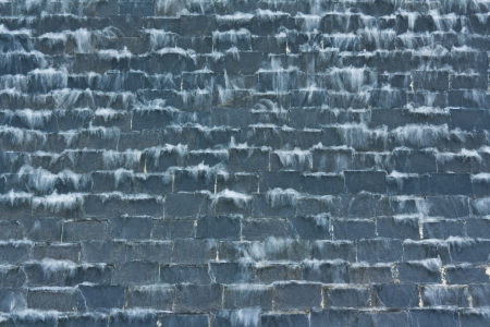 A waterfall on the black stone wall photo