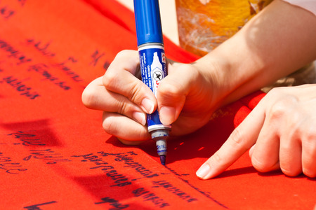 Hand writing letters on red fabrics with blue pen photo