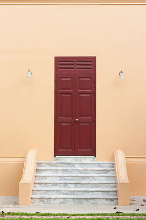 Ancient wooden brown door on orange wall