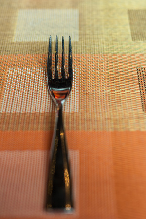 Stainless fork on the colorful napery Stock Photo