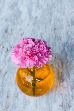 Pink artificial flower in brown round bottle on marble floor.