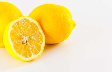 Three lemons, one cut in half Looks fresh and tasty. Against a white backdrop