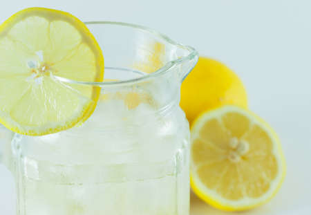 Lemon juice with ice in a glass jug Decorated with lemon slices With lemon cubes cut in half On a white backdrop