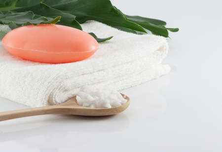 Bar soap on clean white towels, green leaves and salt scrub on white scenes for hygiene.