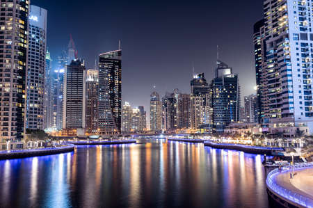 28th JAN, 2021 DUBAI. Dubai Marina skyline with illuminated sky scrappers,buildings and moving boats showing reflection on water captured from Marina Mall , Dubai, UAE. Éditoriale