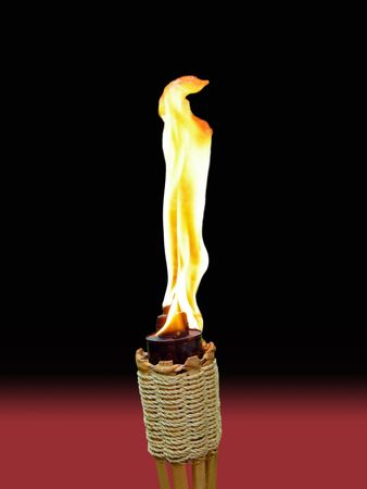 tiki torch with brilliant flame on black and red background photo