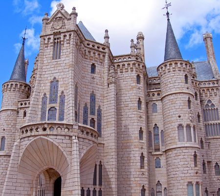 fairytale castle with turrets and stainglass windows set against blue sky photo
