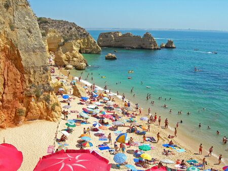 busy beach with colorful umbrellas extending along cliff coastline