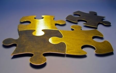 four gold coloured puzzle pieces on blue-grey background