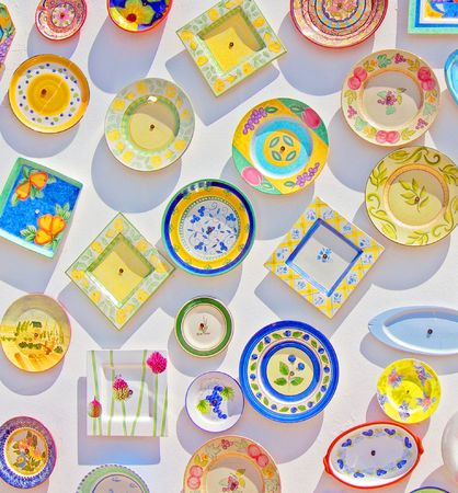 an array of brightly coloured ceramic plates on white backdrop with sun casting shadows Stock Photo