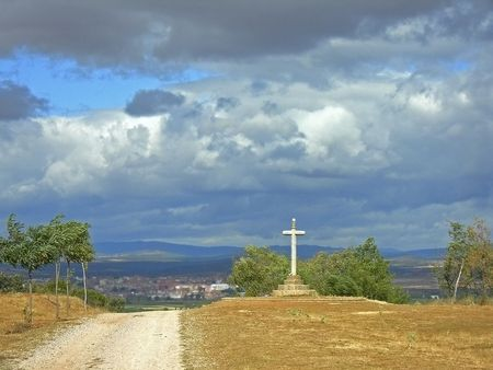 brooding: religious cross next to path overlooking a city covered in dark brooding clouds