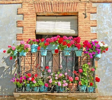 balcony: red and pink flowers in blue pots on weathered brick window Stock Photo