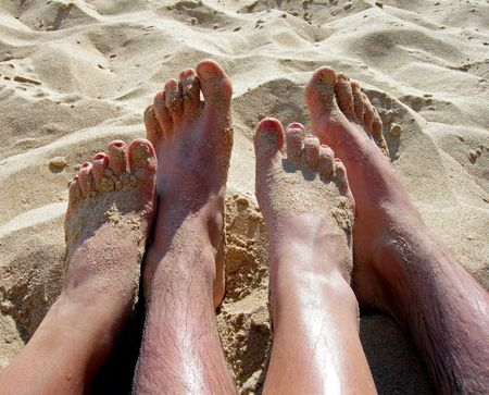 close up of couples feet nestled together on sandy beach photo