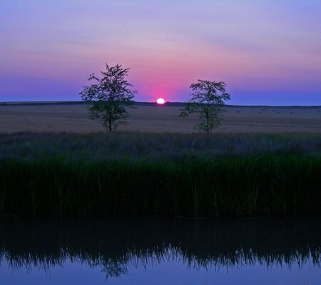 pink sun rising between two trees reflecting on river below Stock Photo