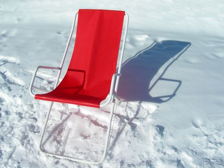 bright sun casts shadows on red chair in the snow photo