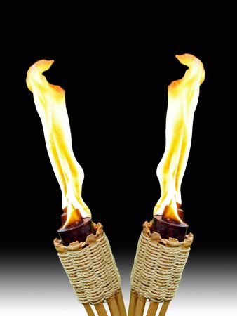two burning tiki torches crossed together on white and black background