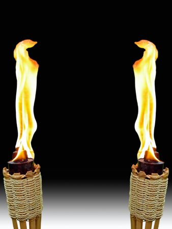 two burning tiki torches opposite one another on white and black background