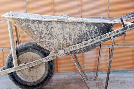 restoring: close up of well used wheelbarrow against a brick wall