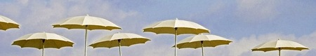 patio deck: line of gold beach umbrellas on a cloudy blue sky Stock Photo
