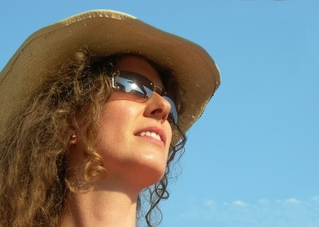 young beautiful woman wearing sunglasses and hat gazes into the sun Stock Photo