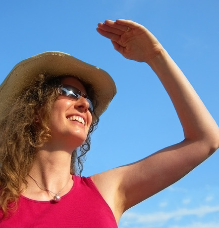 facial features: young pretty woman looks into the sun and smiles Stock Photo